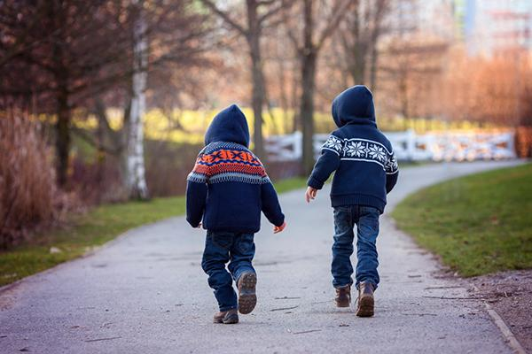 A rear view of two young boys wearing winter hoodies walking down a path.