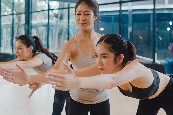 Asian female coach helping youth female athletes stretch indoors.