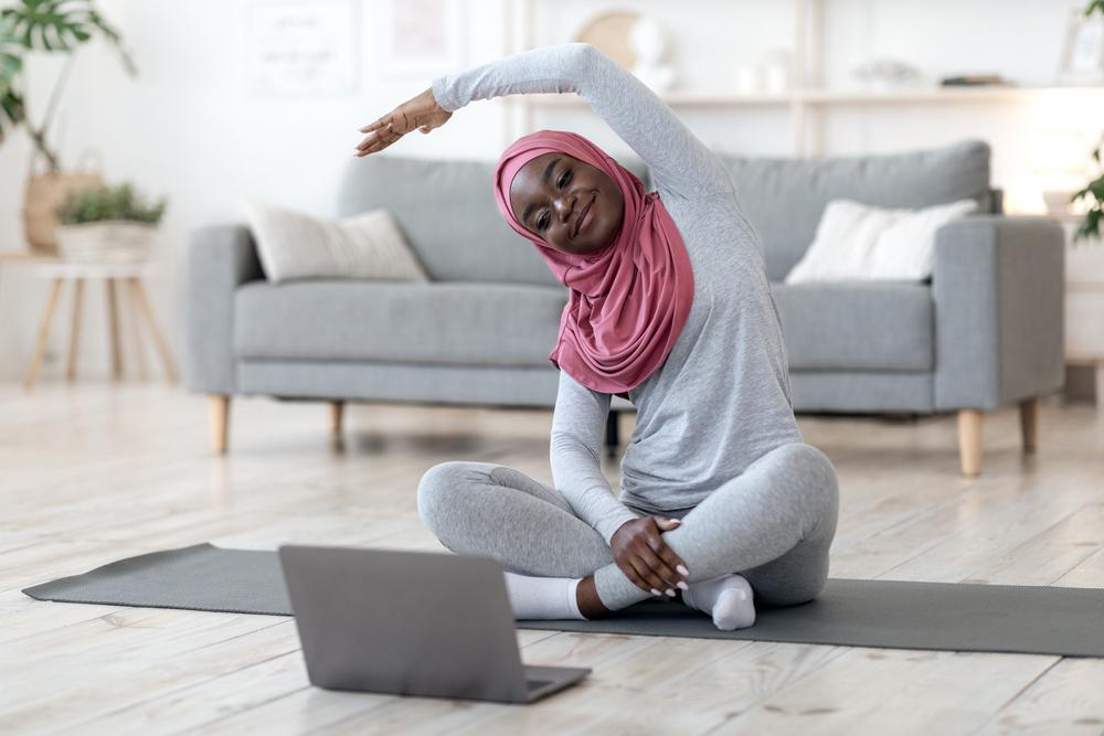 Young black woman wearing a hijab stretching in front of a laptop in her home.