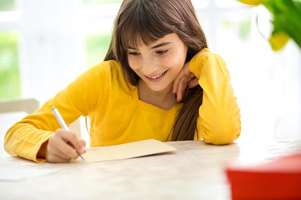 Young girl writing a letter at a desk.