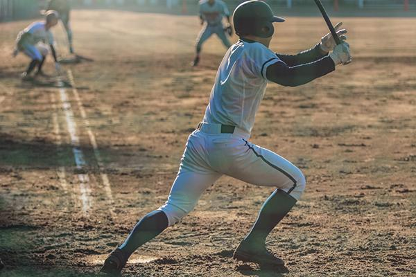 A young baseball player running after a hit.