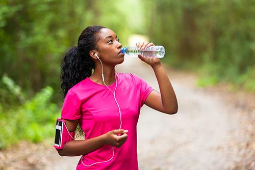 Young woman drinking water on a run.