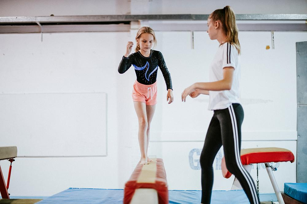 Young female gymnast training on balance beam.