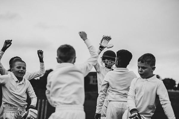 Young team of male cricket players celebrating.
