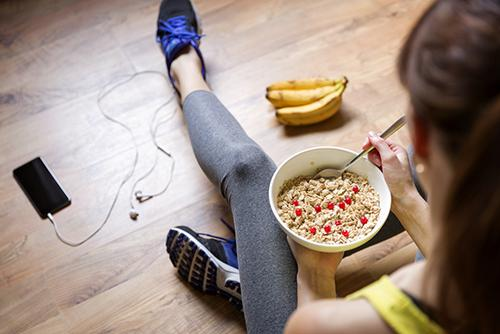Young woman eating meal after a workout.