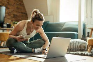 Young woman in workout clothes on laptop in living room.