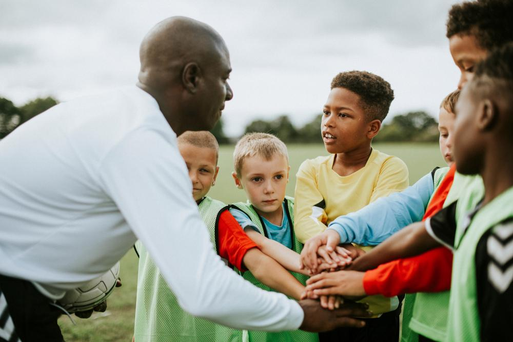 Black coach doing a huddle with youth sports team.